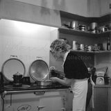 Lee Miller cooking in her kitchen at Farleys